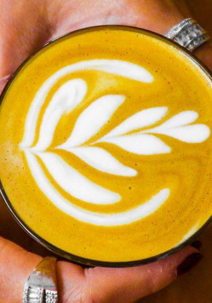 A Woman holding a latte art coffee